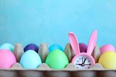复活节raznotsvetny鸡蛋和桃红色闹钟有一只兔子的耳朵的在蓝色背景 图库摄影