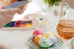 复活节、假日、传统、技术和人概念-接近有拍照片的智能手机的妇女手 免版税图库摄影