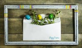 复活节上色了在一个邮政信封的鸡蛋在木背景 免版税图库摄影