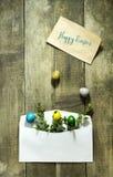 复活节上色了在一个邮政信封的鸡蛋在木背景 免版税库存图片