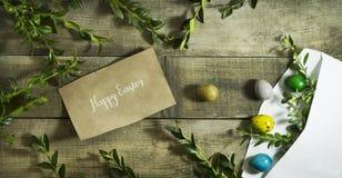 复活节上色了在一个邮政信封的鸡蛋在木背景 免版税库存照片