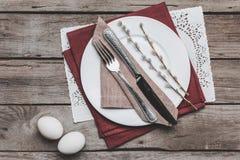 复活节与利器、柔荑花和复活节彩蛋的桌设置顶视图在木桌上 免版税库存照片