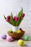 复活节与巢的桌焦点和在花po的桃红色郁金香 免版税库存照片