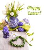 复活节与白色郁金香的贺卡在紫色水罐和matchin 免版税库存图片