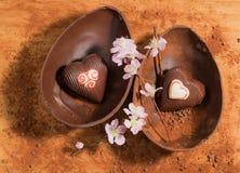 复活节与装饰的两心脏惊奇的朱古力蛋,洒与可可粉和杏仁开花 库存图片
