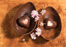 复活节与装饰的两心脏惊奇的朱古力蛋,洒与可可粉和杏仁开花 免版税图库摄影