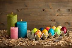 复活节五颜六色的鸡蛋和蜡烛 库存照片