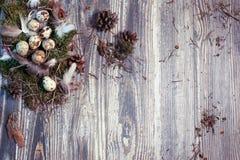 复活节信件装饰用鹌鹑蛋、gnezom、青苔、羽毛、杉木杨柳的锥体和枝杈在木背景的 免版税图库摄影