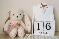 复活节兔子、鸡蛋和woodenPerpetual日历在白色木背景4月16日圣洁复活节2017年 免版税库存照片