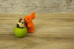 复活节兔子和蛋鹌鹑在立场在木背景 库存照片