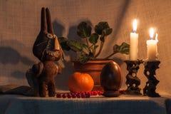 复活节兔子和鸡蛋在黑暗的背景在烛光 免版税库存图片