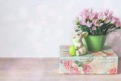 复活节兔子用鸡蛋,在罐的桃红色snowdrops和绿色箱子 免版税库存照片