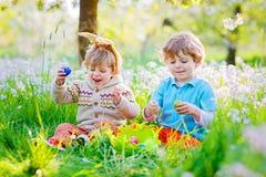复活节兔子耳朵的两个小男孩朋友在鸡蛋期间寻找 免版税库存照片