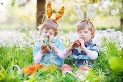 复活节兔子耳朵的兄弟姐妹男孩吃巧克力的 图库摄影