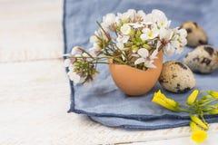 复活节室内装璜,白色黄色花,鹌鹑蛋,蓝色餐巾花束在蛋壳的 图库摄影