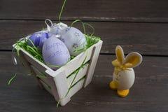 复活节小篮子用色的鸡蛋和一只小蛋兔子在灰色木板 库存图片