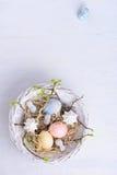 复活节彩蛋、兔宝宝耳朵和merengues在一个圆的篮子,轻的背景 顶上的看法,拷贝空间 免版税库存图片