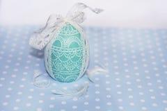 复活节彩蛋与白色丝带的绿色蜡烛 免版税库存图片