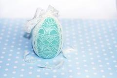 复活节彩蛋与白色丝带的绿色蜡烛 库存图片