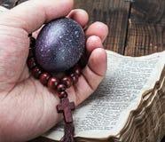 复活节彩蛋和一个念珠在一只手上在一部开放圣经 库存照片