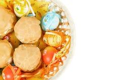 复活节彩蛋和在篮子的自创甜蛋糕 免版税库存图片