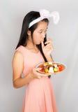 逗人喜爱的亚裔兔宝宝女孩用复活节彩蛋 库存照片