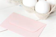 复活节彩蛋和桃红色信封 免版税库存照片