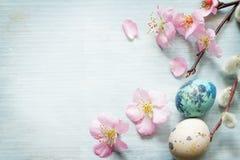 复活节彩蛋和樱花减速火箭的蓝色背景 免版税库存图片