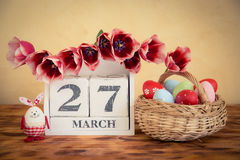 复活节彩蛋和花篮子在木桌上 免版税图库摄影