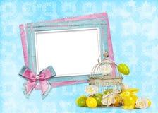 复活节彩蛋和滑稽的兔宝宝与框架在蓝色背景 免版税图库摄影