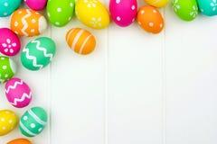 复活节彩蛋在白色木头的角落边界 库存照片