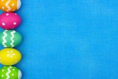 复活节彩蛋在蓝色粗麻布背景的边边界 免版税图库摄影