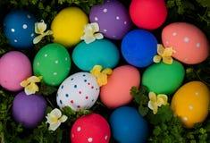 复活节彩蛋手画在与花的绿草 愉快的复活节 免版税库存图片