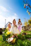 复活节彩蛋狩猎的孩子与兔宝宝 免版税图库摄影