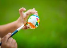 绘复活节彩蛋的儿童手 库存照片