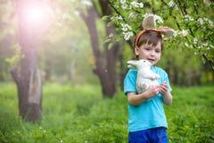 复活节彩蛋的小男孩狩猎在春天庭院里在天 逗人喜爱 图库摄影