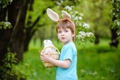 复活节彩蛋的小男孩狩猎在春天庭院里在天 逗人喜爱 库存图片