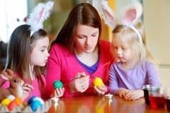 年轻绘复活节彩蛋的母亲和她的两个女儿 免版税图库摄影
