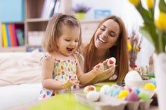 绘复活节彩蛋的母亲和她的婴孩 免版税图库摄影