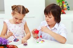 绘复活节彩蛋的男孩和女孩 免版税库存照片