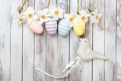 复活节彩蛋,在白色木背景的新鲜的春天黄水仙 看板卡复活节 免版税图库摄影