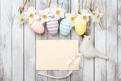 复活节彩蛋,在白色木背景的新鲜的春天黄水仙 看板卡复活节 免版税库存图片