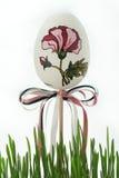 复活节彩蛋绘与与弓的一朵花在草 免版税库存照片