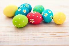 复活节彩蛋 在白色木书桌选择聚焦的五颜六色的复活节彩蛋 顶视图,水平 库存图片