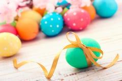 复活节彩蛋 在白色木书桌选择聚焦的五颜六色的复活节彩蛋 顶视图,水平 免版税库存照片