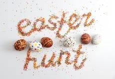 复活节彩蛋寻找由五颜六色的烘烤鸡蛋糖和行做的词组  免版税图库摄影