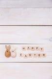复活节快乐的词在木立方体和鸡蛋被写 在白色木背景的愉快的复活节概念 免版税库存图片