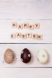 复活节快乐的词在木立方体和鸡蛋被写 在白色木背景的愉快的复活节概念 免版税库存照片