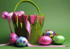 与五颜六色的春天题材圆点的复活节彩蛋狩猎运载篮子袋子和巧克力复活节彩蛋 库存照片