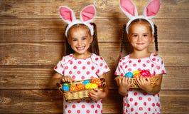 复活节快乐!作为与e的兔子打扮的逗人喜爱的孪生女孩姐妹 免版税图库摄影